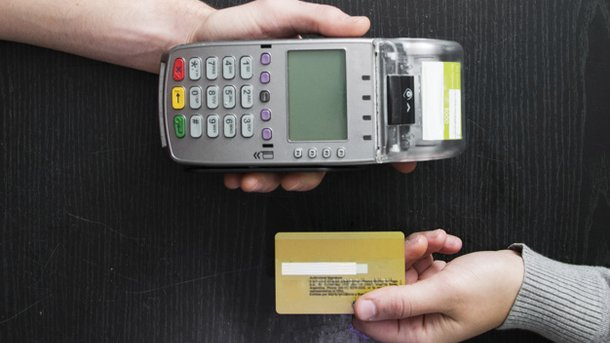 overhead-view-of-hands-holding-card-reader-and-credit-card-on-wooden-table 23-2147874449